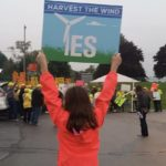woman holding 'harvest the wind' sign